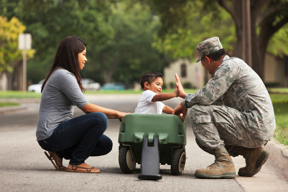Male servicemember in uniform kneeling beside a wagon with a child inside. Female spouse in civilian clothes kneels on the opposite side of the wagon.