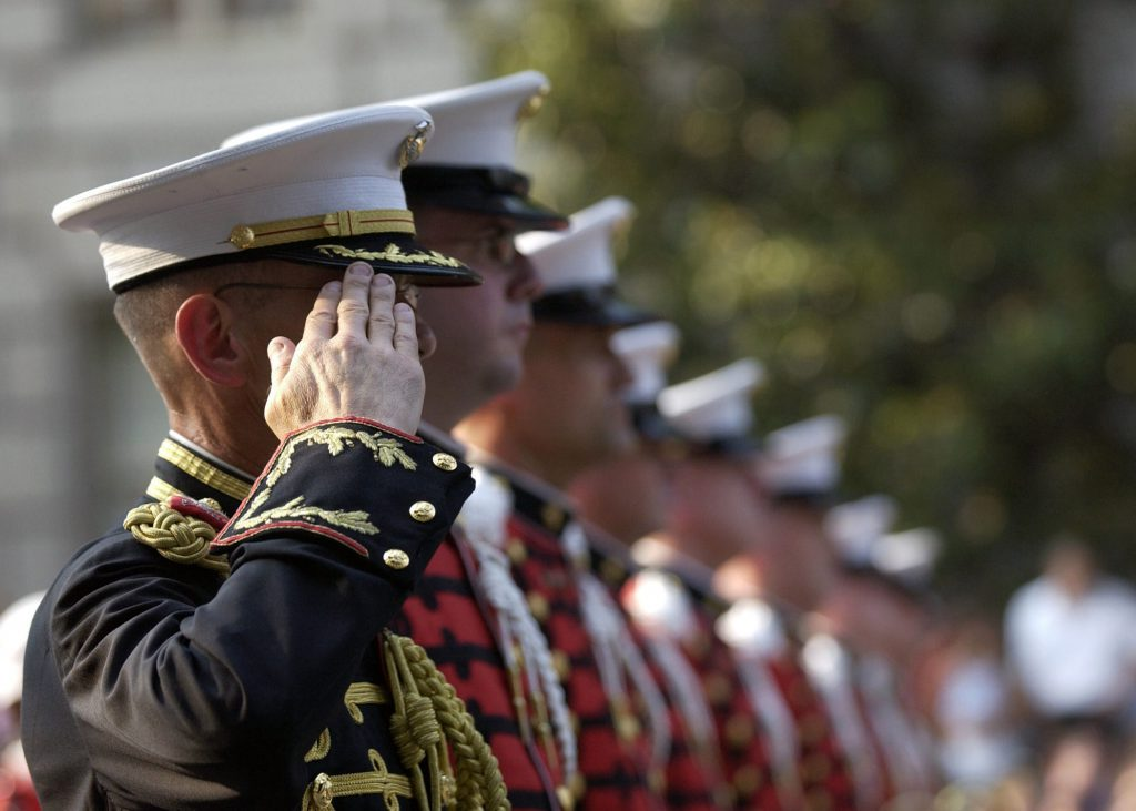Military members in service dress - first one in line is rendering a salute.