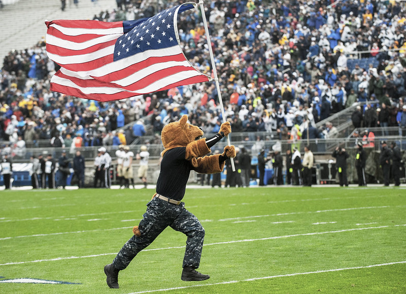 Nittany Lion mascot runs the field holding the American flag at a Military Appreciation football game.